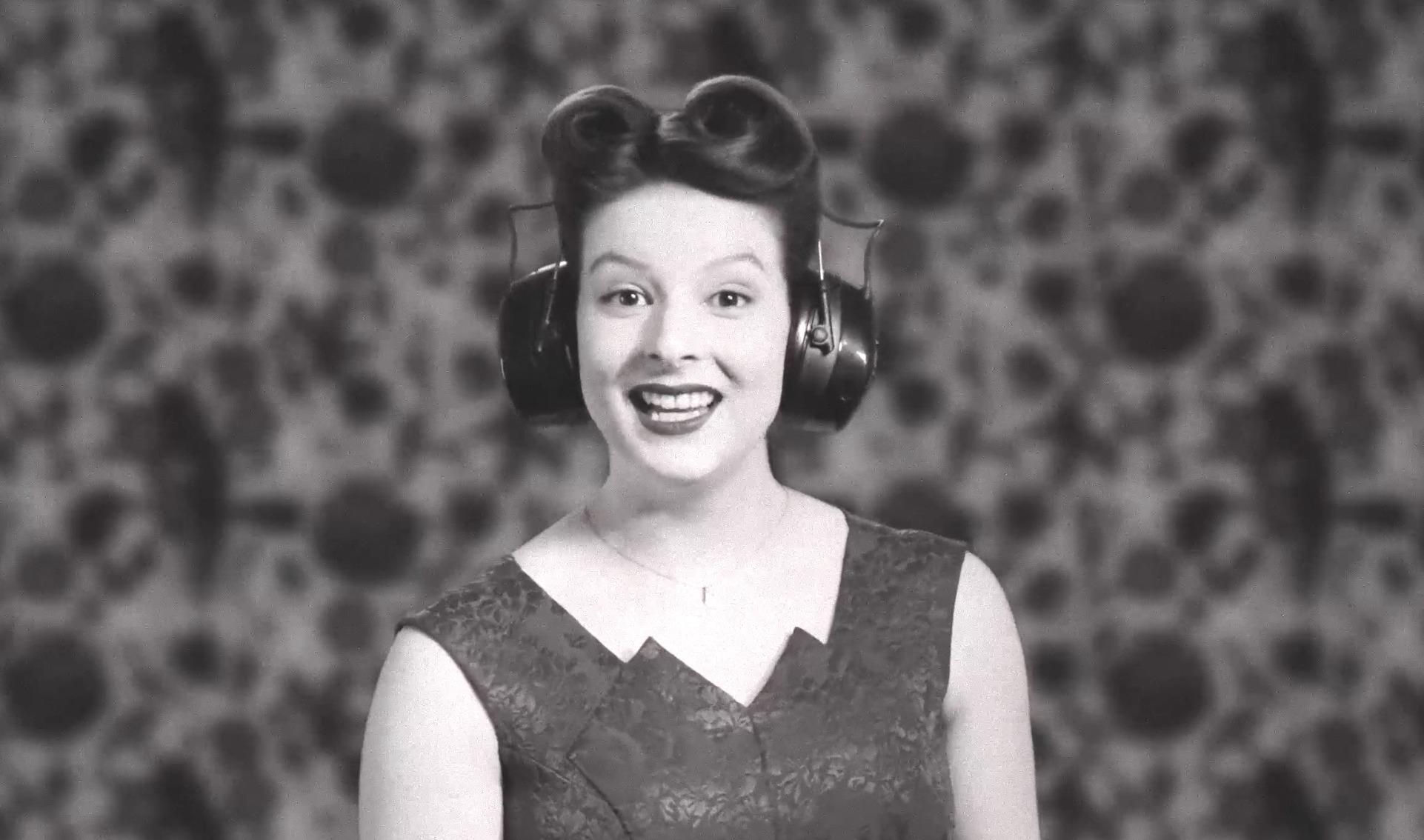 Frau im Kostüm und Frisur der 1940er-Jahre trägt einen modernen Kopfhörer